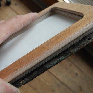Hier mal alles zusammen: Blende innen, eigentlicher Rahmen, noch mit Schutzfolie beklebtes Acrylglas, Messingblende außen.